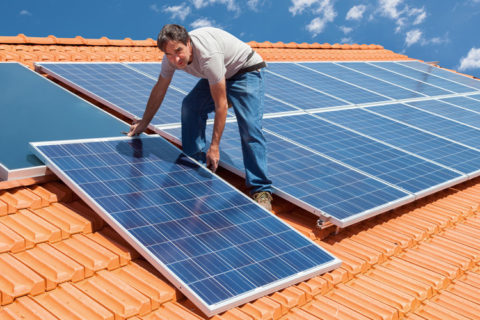 Man Placing Solar Panels on Roof